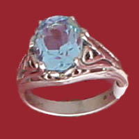 Item #121-RS-RTA- Open Work Ring features an oval 10x8m.m Sky Blue topaz faceted gemstone.